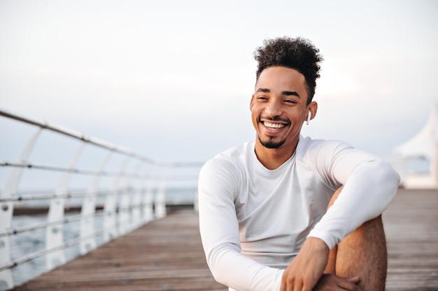 Vrolijke, gekrulde, donkere man in een wit t-shirt met lange mouwen lacht oprecht en rust in de buurt van zee