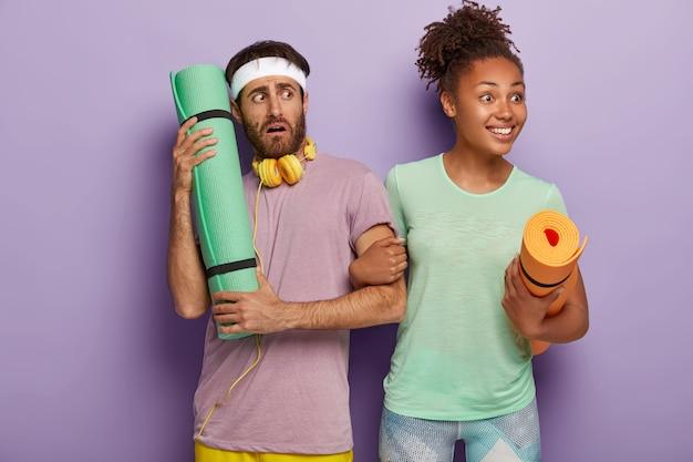 Vrolijke gekrulde jonge afro-amerikaanse vrouw kijkt positief opzij, houdt hand van vriend vast, draagt mat, verbaasd bezorgd man draagt hoofdband, gebruikt koptelefoon aangesloten op een apparaat