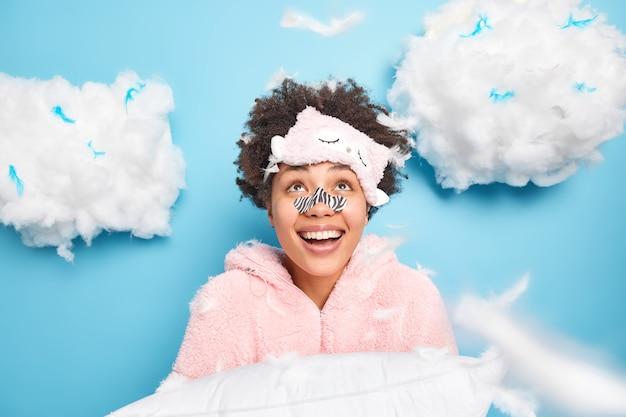 Vrolijke gekrulde jonge vrouw draagt applicatormasker op neus gekleed in nachtkleding kijkt graag boven glimlacht in het algemeen houdt kussen voorbereidt op slaap en rust geïsoleerd over blauwe muur
