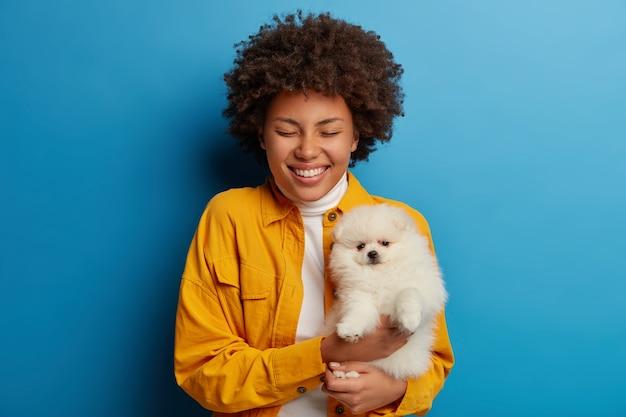 Vrolijke gekrulde jonge vrouw houdt witte rashond op handen, houdt de ogen gesloten, brede glimlach, gekleed in modieuze kleding, geïsoleerd op blauwe achtergrond.