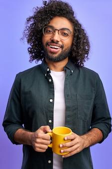 Vrolijke gekrulde man begint de dag met een kopje thee of koffie, hij lacht naar de camera, het dragen van vrijetijdskleding, positieve man geïsoleerd over paarse ruimte
