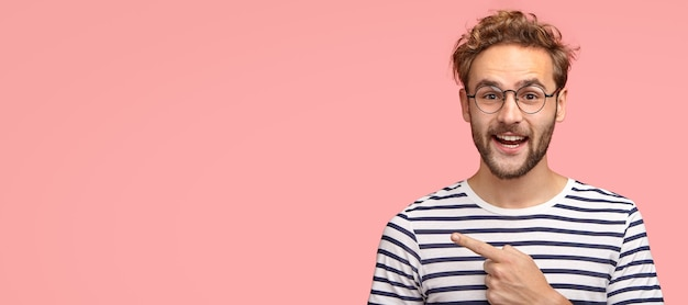 Vrolijke gekrulde man met haren, wijst naar links, draagt vrijetijdskleding en een bril