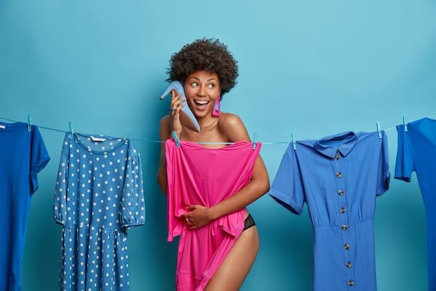 Vrolijke gekrulde vrouw houdt schoen met hoge hakken bij het oor, staat uitgekleed, verbergt het naakte lichaam achter jurk, jurken voor speciale gelegenheid, kijkt vrolijk opzij, geïsoleerd op blauwe muur, kiest outfit