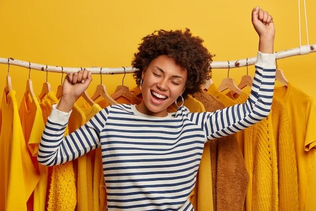 Vrolijke gekrulde vrouwelijke shopaholic danst met opgeheven armen, lacht vrolijk, beweegt actief, poseert tegen rek met gele kleren.