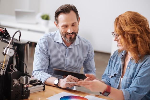 Vrolijke gelukkig aardige man die een tablet vasthoudt en met zijn vrouwelijke collega werkt terwijl hij bij haar zit