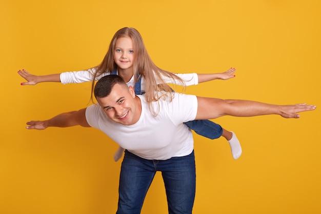Vrolijke gelukkig man verbeeldt zich met zijn mooie dochter om te vliegen als een vliegtuig, poseren geïsoleerd op geel. schot, gelukkige momenten met de beste vader, saamhorigheid, familieconcept.