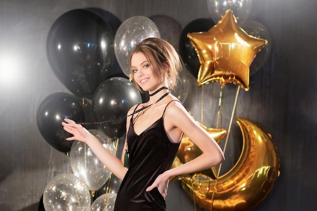 Vrolijke gelukkig mooie jonge vrouw lacht op partij zwarte achtergrond. feest-, vakantie-, kerst- en verjaardagsconcept. confetti. model in een zwarte jurk lachend rond confetti, sneeuw en ballonnen