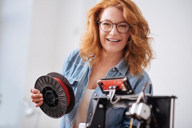 Vrolijke gelukkige aardige vrouw die een gloeidraadspoel vasthoudt en naar je kijkt terwijl ze werkt als 3d-ontwerper