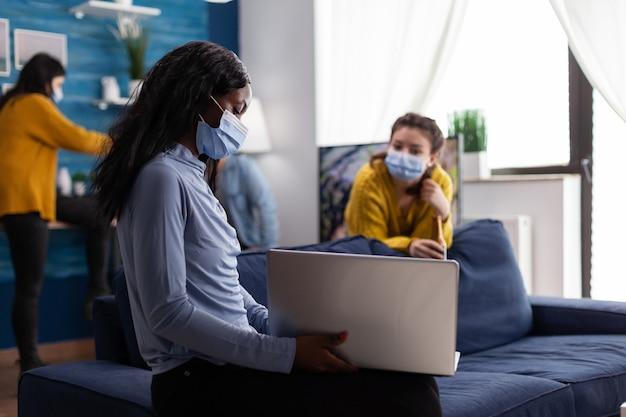 Vrolijke gelukkige afrikaanse vrouw die video op laptop laat zien aan een vriend terwijl ze rondhangt in de woonkamer van een appartement en sociale afstand houdt als gevolg van een pandemie van het coronavirus om verspreiding van het virus te voorkomen.