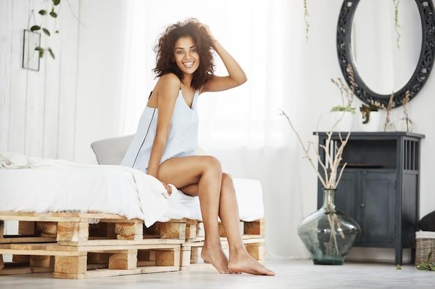Vrolijke gelukkige afrikaanse vrouw in nachtkleding glimlachend zittend op bed thuis.
