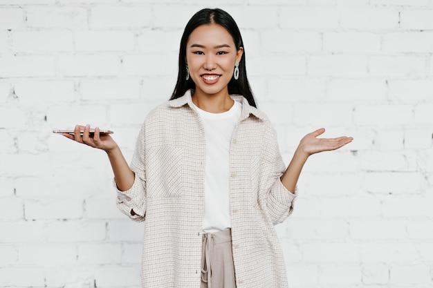 Vrolijke gelukkige aziatische vrouw in beige vest, broek en t-shirt houdt telefoon vast