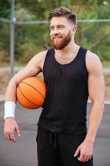 Vrolijke gelukkige basketbalspeler die buiten met bal staat