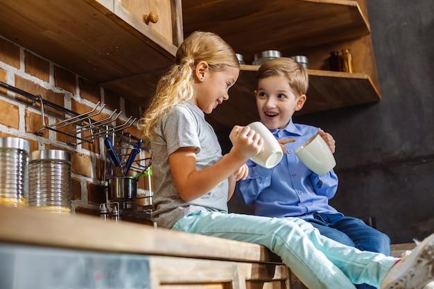 Vrolijke gelukkige broers en zussen zitten in de keuken terwijl ze thee drinken
