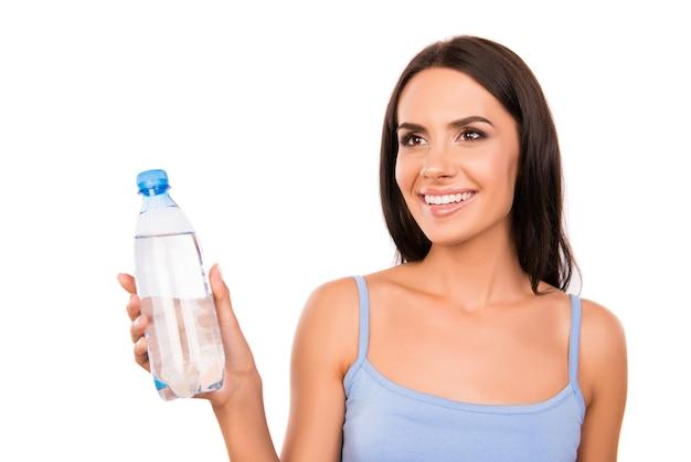 Vrolijke gelukkige brunette die een fles met zoet water houdt