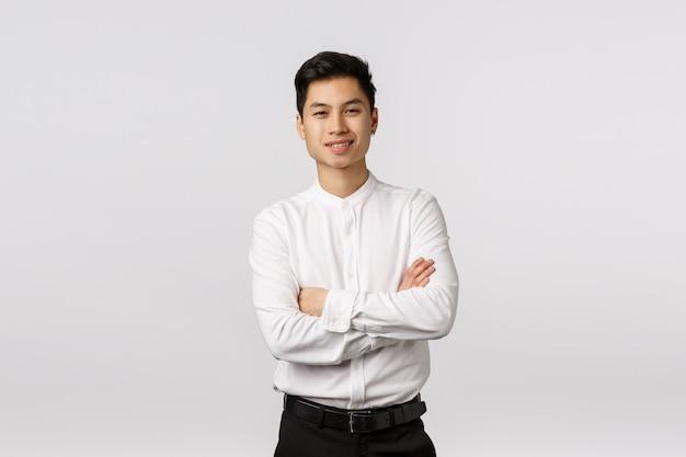 Vrolijke, gelukkige en succesvolle knappe aziatische jonge mannelijke ondernemer, klaar met business school en klaar om elke taak uit te voeren, armen over elkaar, glimlachend tevreden