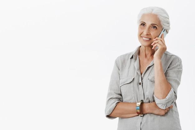 Vrolijke gelukkige grootmoeder praten op mobiele telefoon en glimlachen