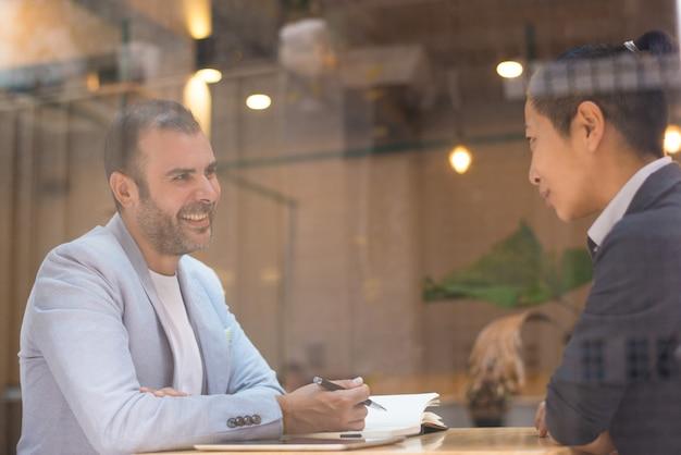 Vrolijke gelukkige h-manager die aan vrouwelijke kandidaat in koffie spreekt
