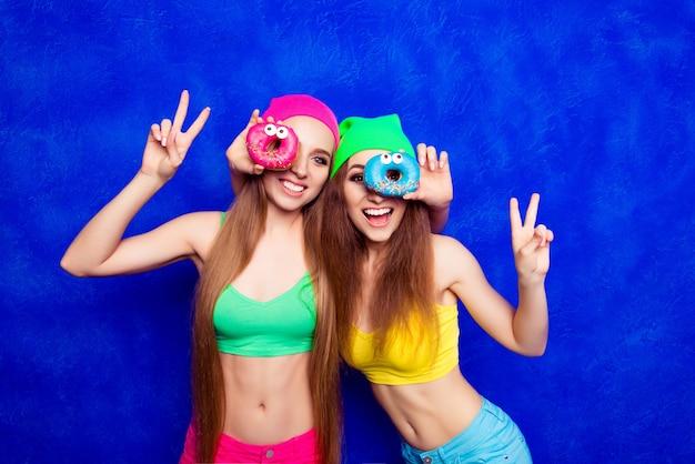 Vrolijke gelukkige hipster zusters die plezier hebben en donutes houden