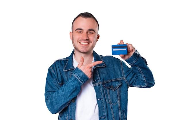 Vrolijke gelukkige jonge man wijzend op creditcard Premium Foto