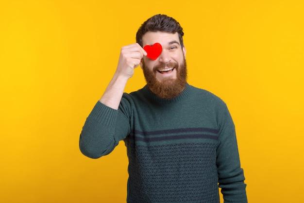 Vrolijke gelukkige jonge mens die rood document hart over zijn ogen houdt