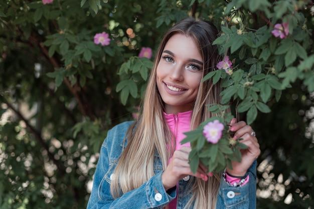 Vrolijke gelukkige jonge vrouw met een mooie glimlach met lang haar in een modieus blauw denim jasje ontspant in de buurt van een struik met bloemen buiten in de stad. vrolijk aantrekkelijk meisje geniet van zomerweekend.