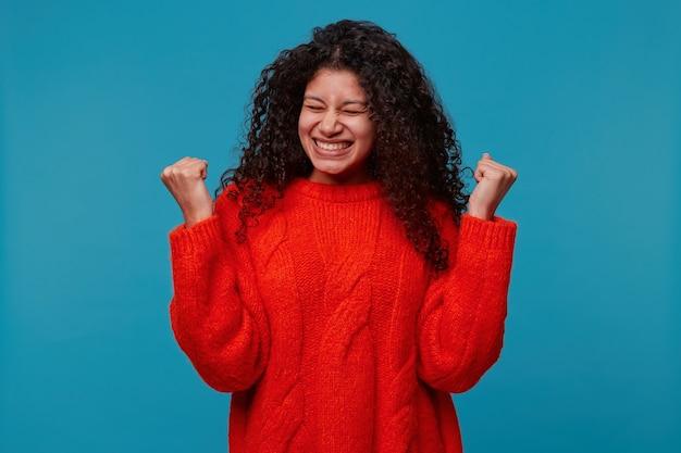 Vrolijke gelukkige jonge vrouw met mooi krullend zwart haar toont gebaar van overwinning