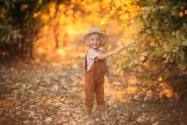 Vrolijke gelukkige jongen in een zomerhoed op een wandeling in het bos