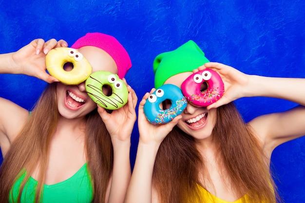 Vrolijke gelukkige komische zusters die donutes tegen de ogen houden