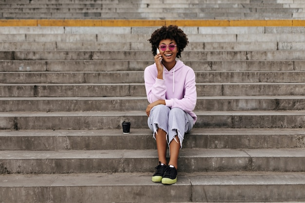 Vrolijke gelukkige krullende vrouw in stijlvolle jeans, oversized hoodie en roze zonnebril glimlacht, praat aan de telefoon en zit buiten op trappen