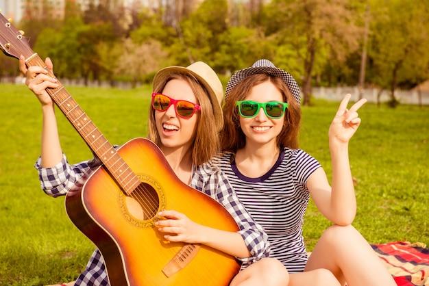 Vrolijke gelukkige meisjes die picknick hebben en op gitaar spelen