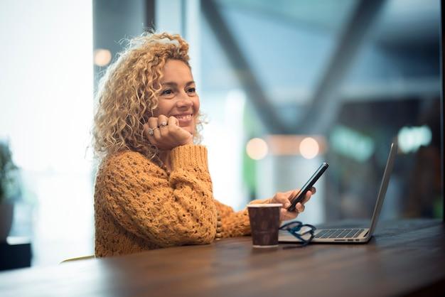 Vrolijke gelukkige mensenvrouwenreiziger wacht bij de luchthavenpoort voor een vertraagde vlucht met behulp van een modern technologisch apparaat als telefoon en laptopcomputer