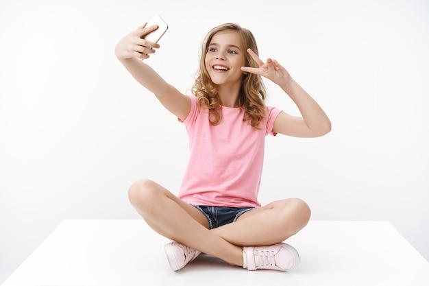 Vrolijke gelukkige mooie tienermeisje zittend gekruiste benen op de vloer, spelen met smartphone toon vrede, overwinning teken mobiele telefoon aan de voorkant, selfie nemen, glimlachend vrolijk energiek, witte muur