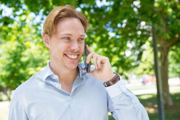 Vrolijke gelukkige ondernemer die van aardig telefoongesprek geniet