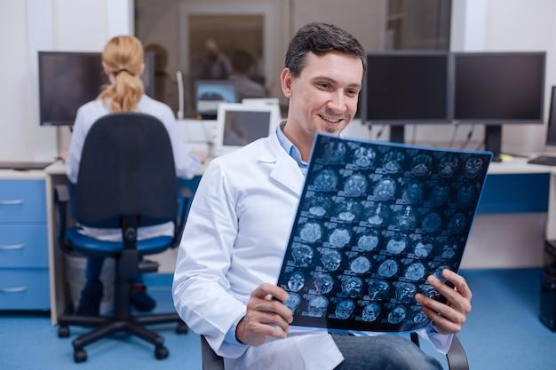 Vrolijke gelukkige professionele arts die de verbetering opmerkt en glimlacht terwijl hij naar het röntgenbeeld kijkt