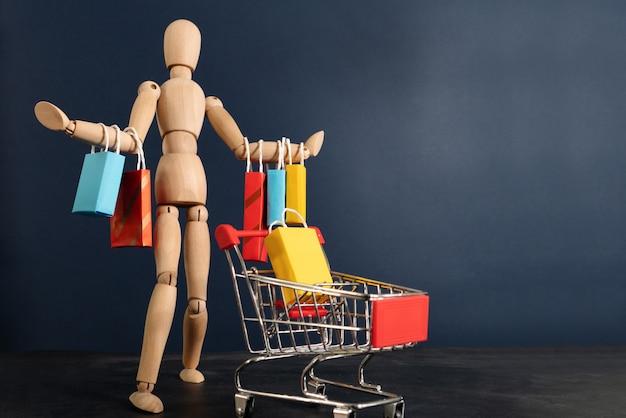 Vrolijke gelukkige shopaholic houten pop met veel boodschappentassen op arm en winkelwagentje