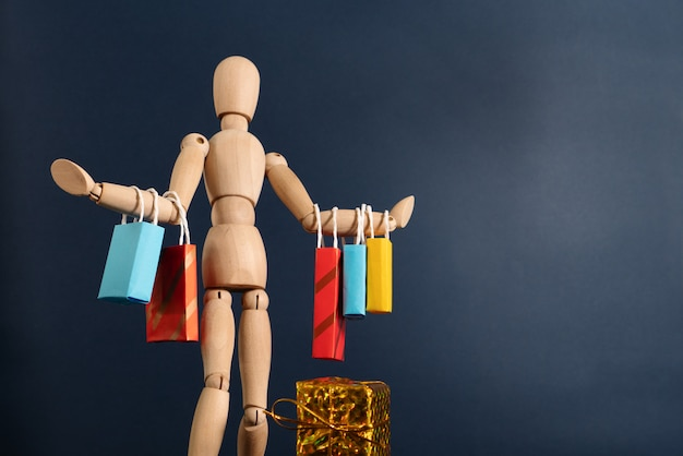 Vrolijke gelukkige shopaholic houten pop met veel boodschappentassen op de arm