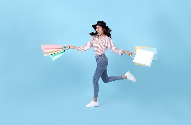 Vrolijke gelukkige tiener aziatische vrouw die van winkelen geniet, ze draagt boodschappentassen en springt in het winkelcentrum.