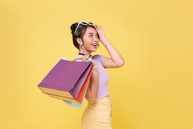 Vrolijke gelukkige tiener aziatische vrouw die van winkelen geniet, ze draagt boodschappentassen in het winkelcentrum.