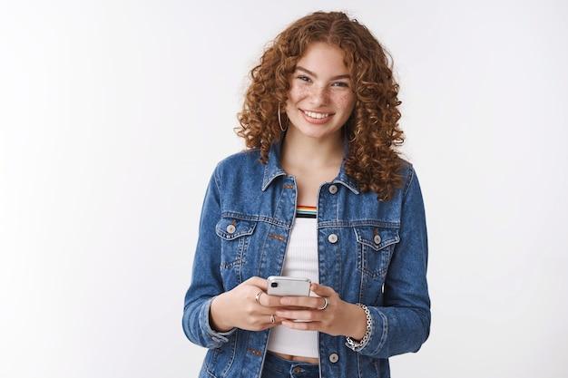 Vrolijke gelukkige tienermeisje met plezier communiceren vriendje via sociale netwerk app houden witte smartphone breed glimlachend camera bestellen outfit voor prom met behulp van shopping website via apparaat