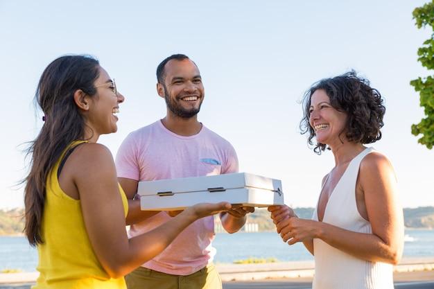 Vrolijke gelukkige vrienden die in openlucht voor picknick samenkomen