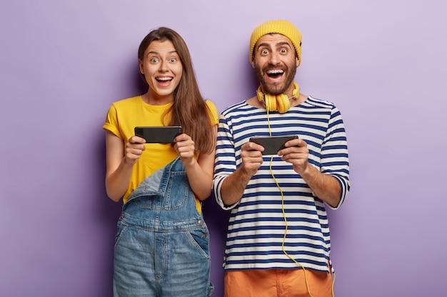 Vrolijke, gelukkige vrouw en man spelen games op smartphone, dagen elkaar uit, surfen op het net
