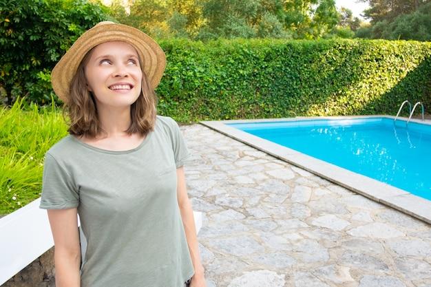 Vrolijke gelukkige vrouw in de zomeruitrusting die zich in tuin bevindt