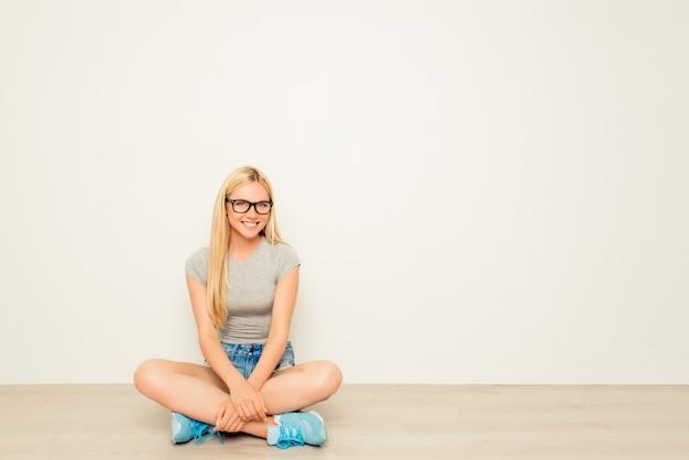 Vrolijke gelukkige vrouw in glazen zittend op de vloer met gekruiste benen