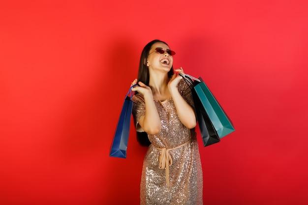 Vrolijke, gelukkige vrouw in rode zonnebril en elegante jurk met veelkleurige pakketten