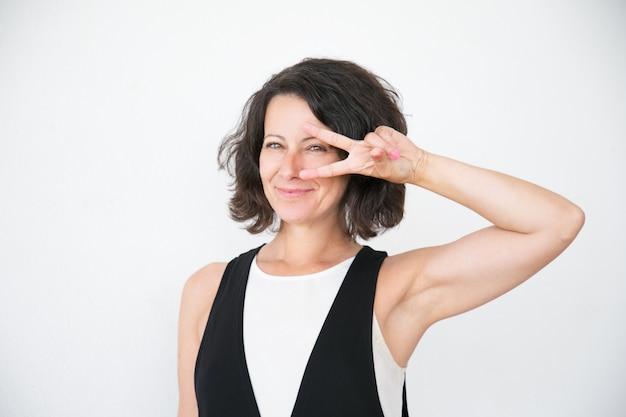 Vrolijke gelukkige vrouw in toevallig tonend vredesteken