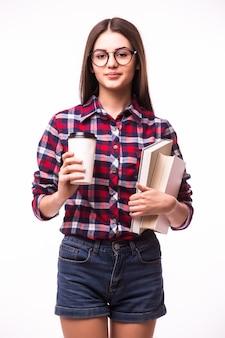 Vrolijke gelukkige vrouw met brede glimlach, draagt afhaalkoffie en een rood boek, blij dat ze klaar is met studeren