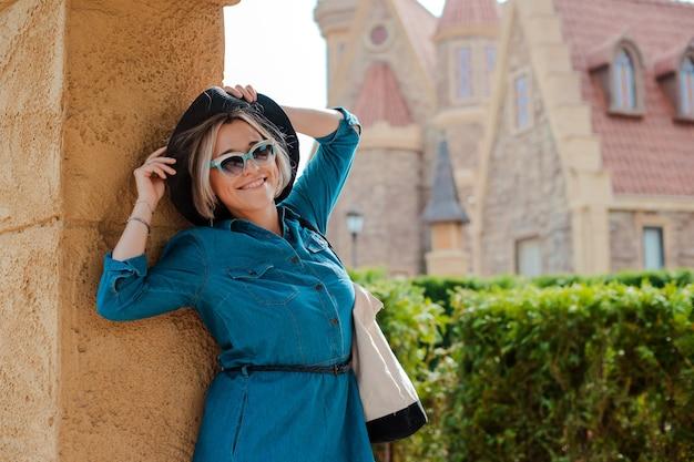 Vrolijke gelukkige vrouw zwerver met trendy look zonnebril tijdens het reizen naar het buitenland in de zomer, vrouwelijke toerist