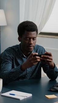 Vrolijke gelukkige zwarte man die videogames speelt op zijn telefoon