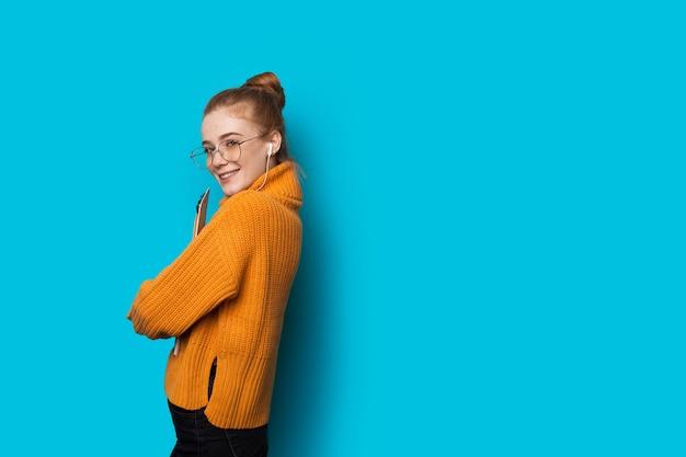 Vrolijke gember kaukasische dame met sproeten en bril is poseren met een laptop en koptelefoon op een blauwe muur met vrije ruimte