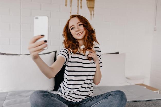 Vrolijke gembervrouw die foto van zichzelf neemt. debonair jonge dame met behulp van telefoon voor selfie.